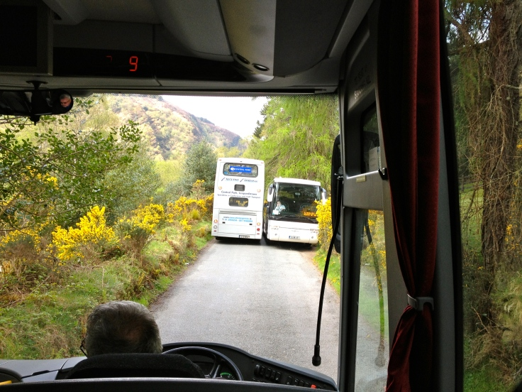 Two giant busses passing each other on a very narrow, one-lane road.